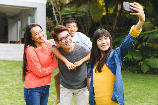 Happy asian parents, son and daughter smiling outdoors and taking selfie in garden