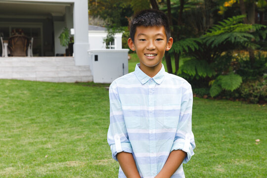 Portrait of smiling asian boy smiling outdoors and wearing casual clothes in garden