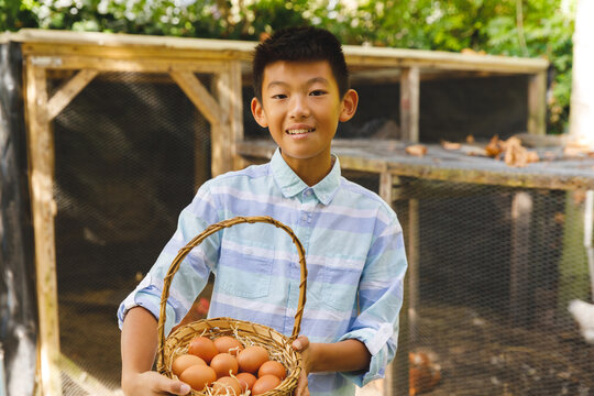 Portrait of asian boy smiling and holding basket, collecting eggs from hen house in garden