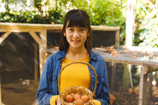 Portrait of asian girl smiling and holding basket, collecting eggs from hen house in garden