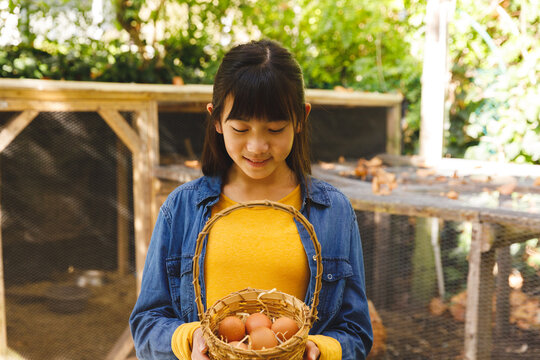 Asian girl smiling and holding basket, collecting eggs from hen house in garden