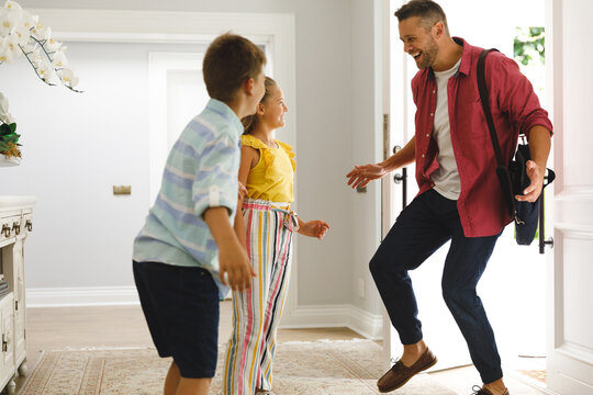 Happy caucasian father returning home with daughter and son smiling and greeting him at front door