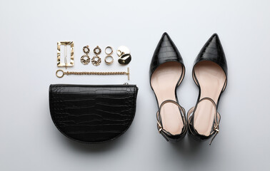 Stylish woman's bag, shoes and bijouterie on light background, flat lay