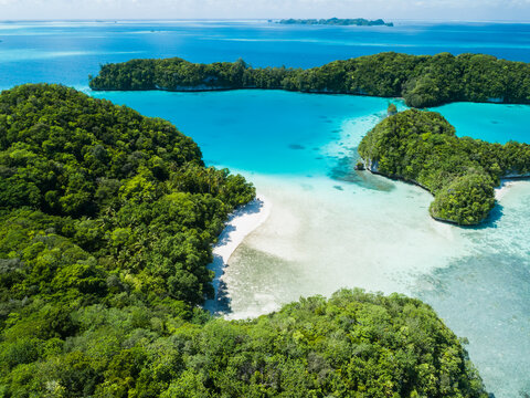 Aerial view of jungle covered limestone islands in Palau with lagoon and beach