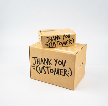 Two closed cardboard boxes taped up, and there is a Thank you for being our customer beside the parcel box for delivery and shopping online concept design isolated on white background.