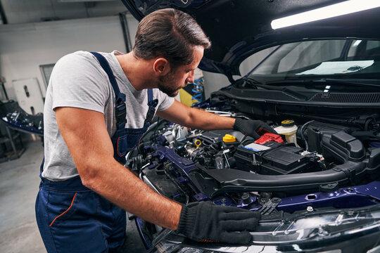 Professional mechanic adjusting red battery under car hood