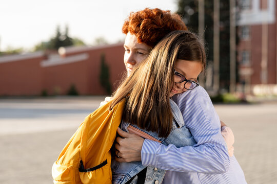 Young woman seeing off her youthful daughter with backpack while both standing in embrace