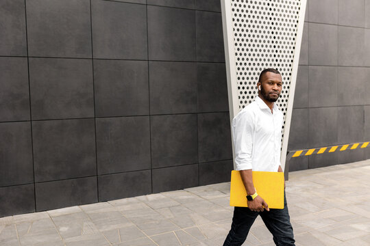 Young adult male student or freelancer in stylish clothes standing with yellow laptop outdoors, walking to the office for business meeting. Serious successful businessman looking at the camera, posing