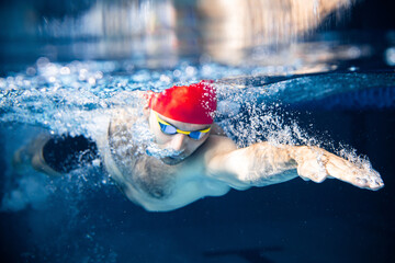 One male swimmer practicing and training at pool, indoors. Underwater view of swimming movements...