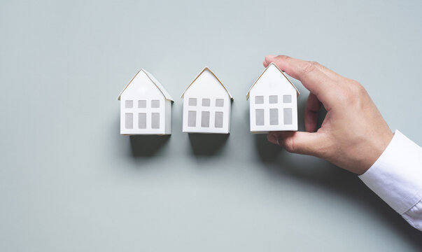 Business property,real estate and investment concepts with investor hand and white model house on pastel color