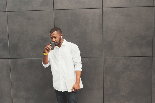 Attractive male in white shirt drinking a cup of coffee or tea, taking a break from office work outdoor. Handsome stylish african american businessman or student looking at camera, hold tablet in arms
