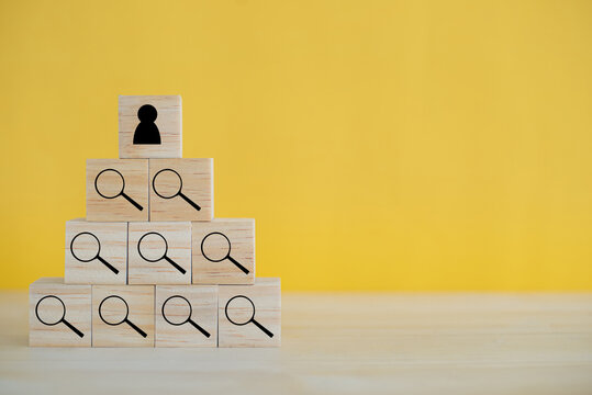 Human resource management and recruitment business concept. Wood cube block on top pyramid on yellow background with copy space.