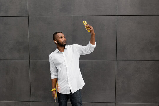 Confident stylish male employee or student using smartphone, having serious video call from colleague. Successful businessman standing outside the office, take a break from work, making a selfie