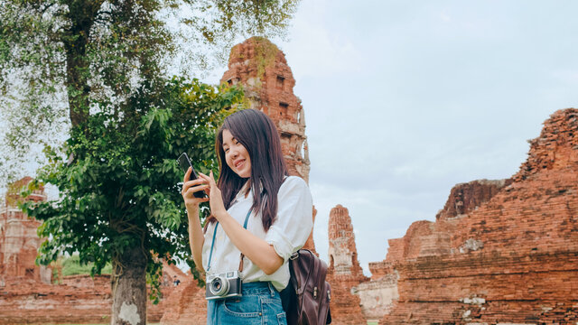 Cheerful beautiful young Asian backpacker blogger woman casual with camera look at photo on smartphone smile with happy face travel pagoda at the old city, Lifestyle tourist travel holiday concept.