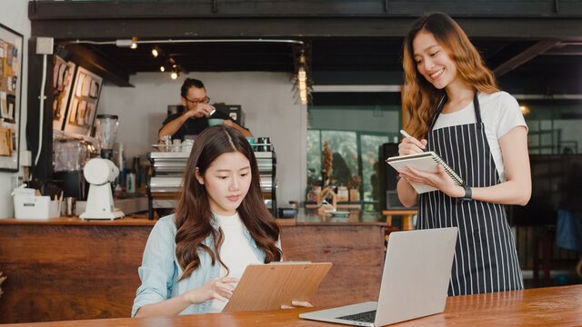 Cheerful Asian lady waitress with notebook taking receive order menu from young client girl at urban cafe. Young Asian freelance women working on laptop at coffee shop. Owner small business concept.