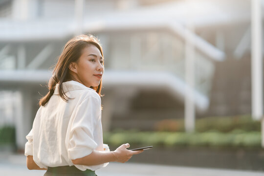 Successful young Asia businesswoman in fashion office clothes holding disposable paper cup of hot drink and using smart phone while walking outdoors in urban modern city. Business on the go concept.