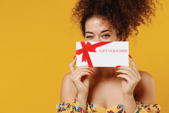 Young happy smiling fun cheerful woman 20s with culry hair in casual clothes hold cover face with gift certificate coupon voucher card for store isolated on plain yellow background studio portrait