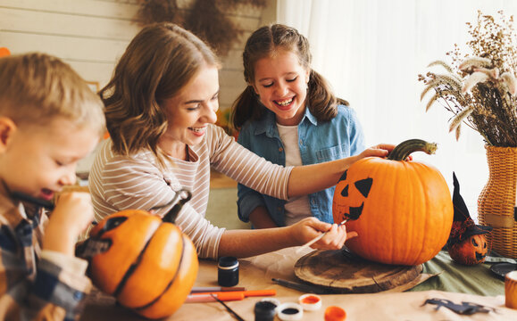 Smiling mother with children creating jack-o-lantern during Halloween celebration at home