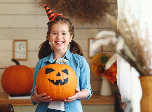 Smiling kid girl in hat showing classic Jack-o-lantern at camera during Halloween celebration