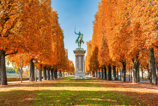 Autumn fall park in Paris city with orange trees and monument of rider with sword