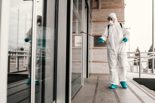 A photo of a male person in a white protective suit and mask disinfects the front door and stairs to the office building with chemical agents. COVID-19 prevention