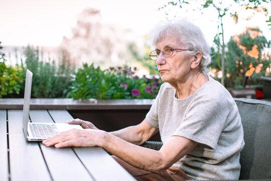 elderly woman using laptop on terrace