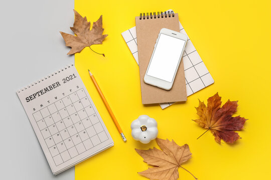 Calendar with mobile phone, notebook and autumn leaves on color background