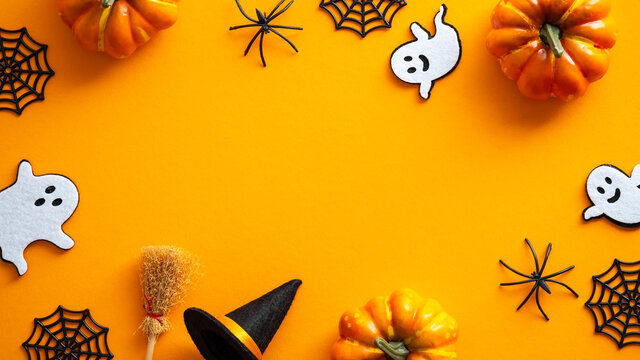 Happy Halloween card design mockup. Flat lay, top view ghosts, spider web, pumpkins, witch hat and broom on orange background.