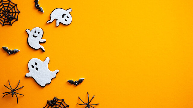 Halloween background with ghosts, bats, spiders, decorations. Halloween party invitation card mockup. Flat lay, top view, copy space.