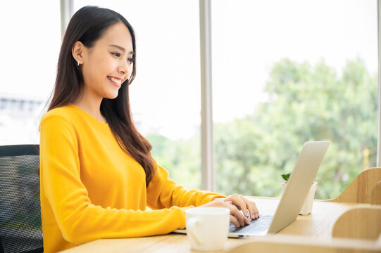 Work at home, Video conference, Online meeting video call, Beautiful young asian woman looking at computer screen watching webinar and working on laptop in home