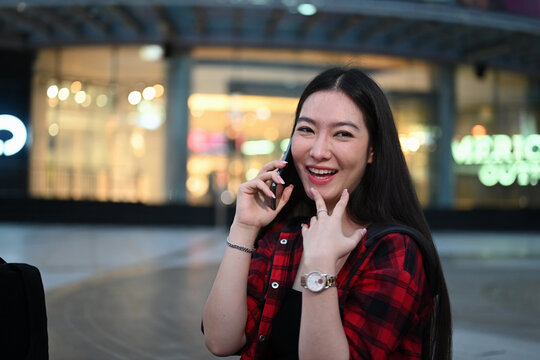 Young Asian woman talking on mobile phone while standing at outdoor shopping mall in the evening.