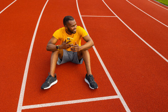 Happy attractive male athlete sitting at the stadium track, relaxing, taking a break after running. Handsome african american man using smartphone, browsing internet, smiling, workout outdoors concept