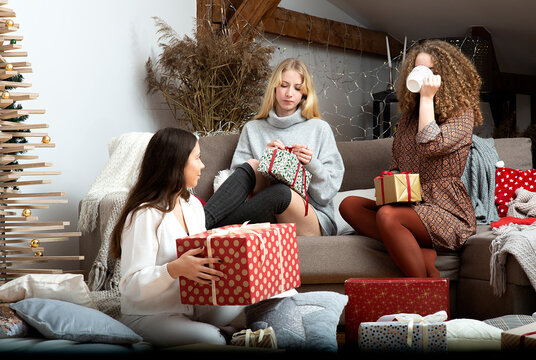 group of young attractive women have fun packing wrapping Christmas presents in a cozy home atmosphe