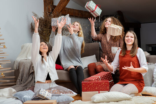 Smiling girls throwing their Christmas gifts in the air