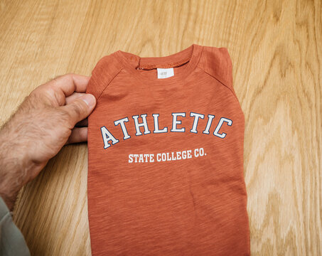 Lyon, France - May 2, 2021: POV male hand father holding infant baby clothes with Atheltic state college co sign manufactured by the H and M Hennes and Mauritz AB