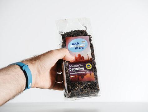 Paris, France - Jul 30, 2017: POV male hand holding package with Das Gesunde Plus from Dm translated as Healthy Plus black darjeeling tea