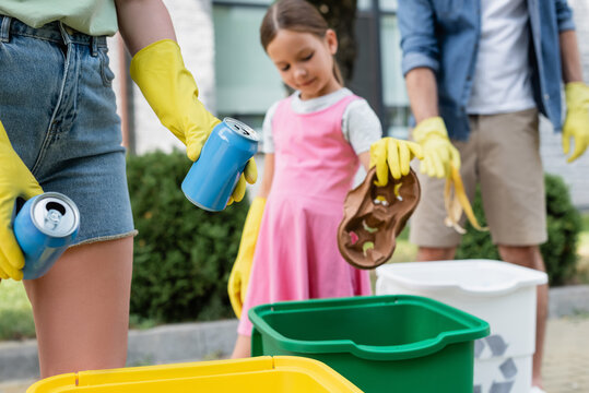 Woman holding tin cans near blurred family and trash bins outdoors