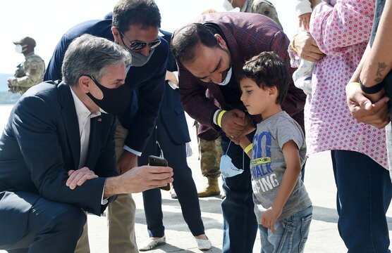 U.S. Secretary of State Antony Blinken shows a picture of his children to a young Afghan refugee at Ramstein Air Base