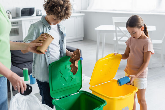 Kids sorting garbage near mother and trash cans with recycle sign at home