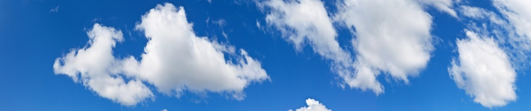 Panoramic view of the blue sky with cumulus clouds on a sunny clear day. White fluffy light clouds float across the blue sky. Heavenly bright landscape. Natural background, banner
