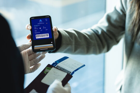 Passenger showing digital boarding pass to airline attendant