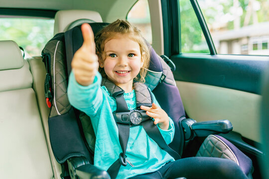 Small child sitting in a car doing thumb up