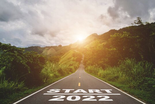 Start new year 2022 text on long country road on top of the mountain with green tree, forest and sunlight in the morning represents a new beginning.