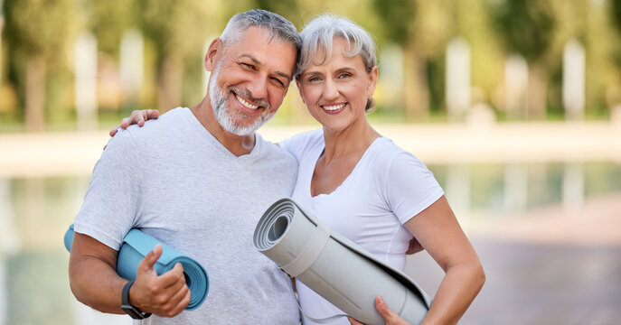 Smiling senior couple husband and wife embracing while standing at park with exercise mats