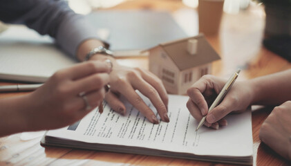 Cropped image of real estate agent assisting client to sign contract paper at desk with house model