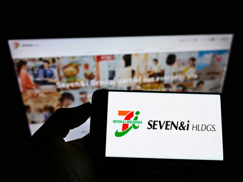 STUTTGART, GERMANY - May 27, 2021: Person holding cellphone with logo of Seven and i Holdings Co. Ltd. on screen in front of website.