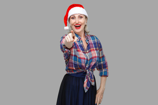 Portrait of happy beautiful adult woman in red santa cap and checkered shirt standing, pointing finger and mocking you with toothy smiling, looking at camera. Indoor, studio shot, yellow background