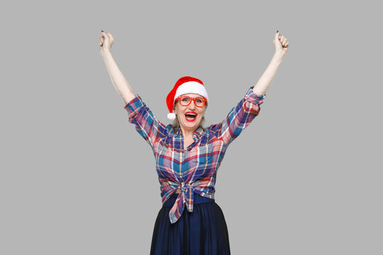 Portrait of funny modern aged woman in red santa cap, and eyeglasses checkered shirt standing with hands up and with surprised face looking at camera. Indoor, studio shot, yellow background