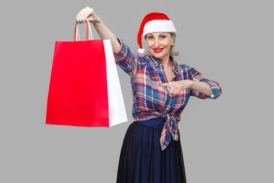 Happy modern middle aged woman in red santa cap and checkered shirt standing, holding and pointing finger to shopping bags and toothy smile, looking at camera. Indoor, studio shot, yellow background