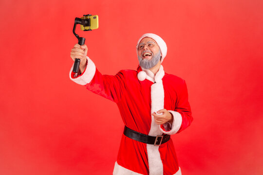 Portrait of happy smiling elderly man with gray beard wearing santa claus costume talking with followers, holding steadicam in hands, livestream. Indoor studio shot isolated on red background.